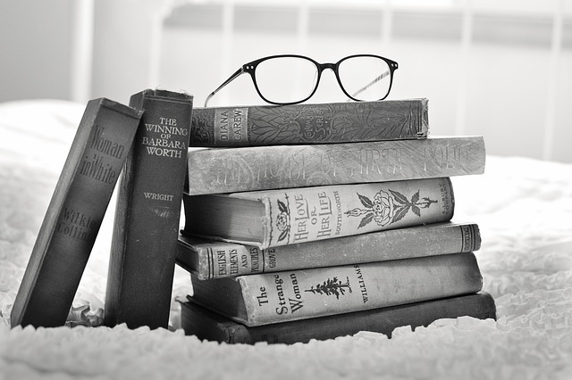 black and white photo stack of books with glasses